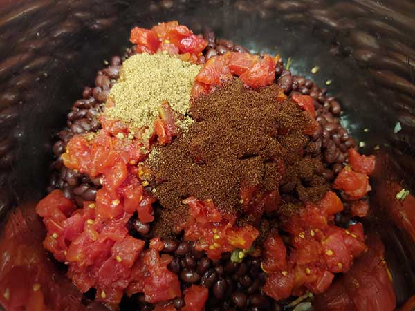 Spices on top of black beans and dice tomatoes.