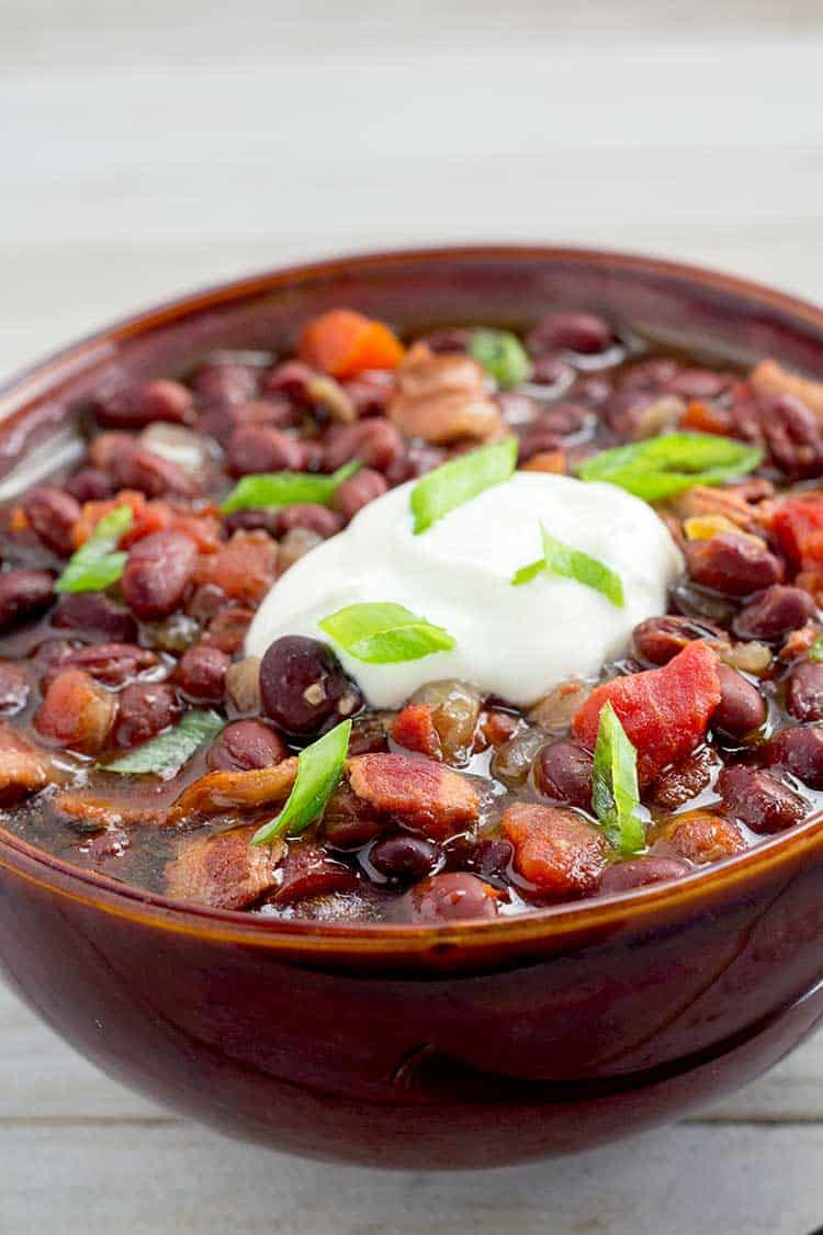 Black bean soup in brown bowl topped with sour cream and green onions.