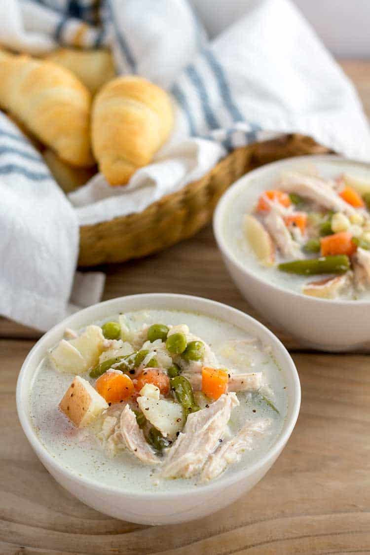 Two bowls of chicken pot pie soup with basket of crescent rolls.