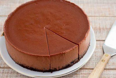 Sliced chocolate cheesecake with spatula.