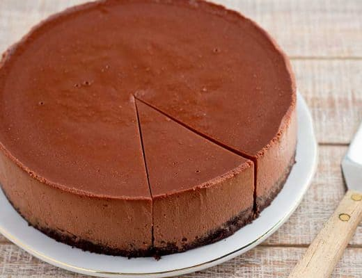 Sliced chocolate cheesecake with spatula.