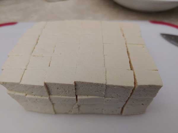 Block of tofu cut into small cubes.