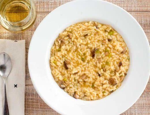 Instant Pot mushroom risotto in white bowl with glass of wine.