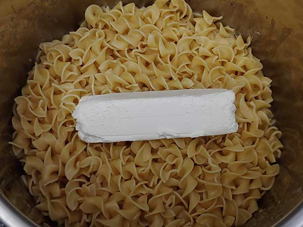 Block of cream cheese on top of cooked egg noodles.