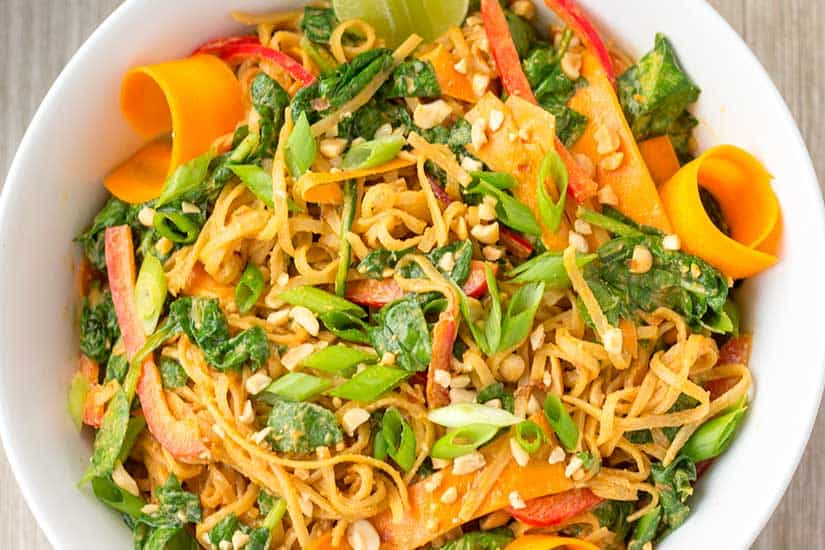Thai Noodle Salad with curls of carrot and sliced limes in white bowl.