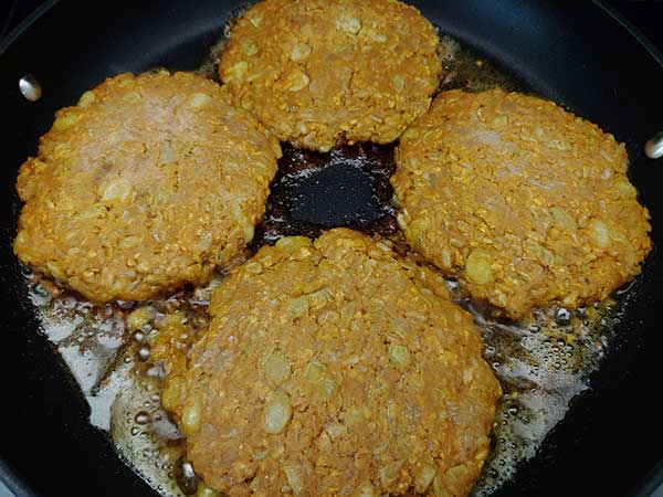 Four frozen bean burger patties frying in nonstick pan.