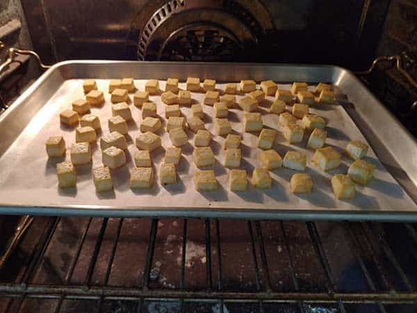 Small pieces of tofu baking in oven.
