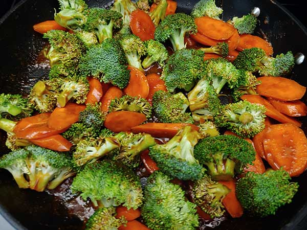 Broccoli florets and sliced carrots cooking in peanut sauce.