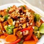 Vegan tofu stir fry in white bowl with chopsticks.