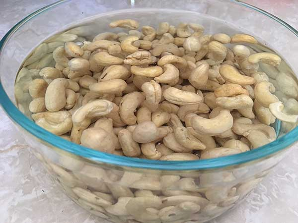 Raw cashews soaking in bowl of water.