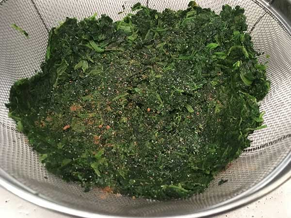 Defrosted chopped spinach in fine mesh strainer, seasoned with salt and nutmeg.