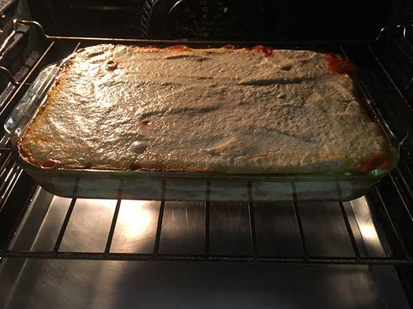 Uncooked lasagna baking in oven.