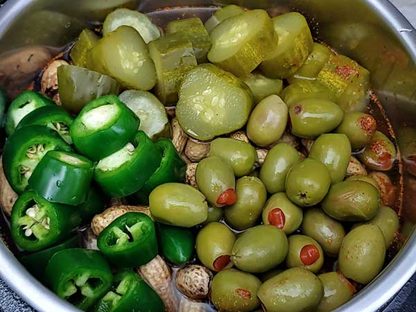 Pickles, jalapenos, and olives on top of peanuts in Instant Pot.