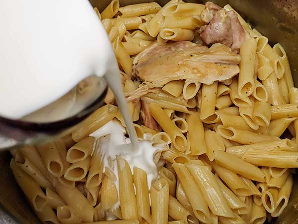 Pouring cream over chicken and pasta.