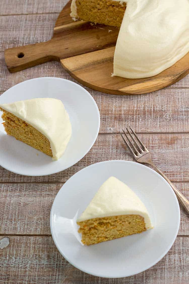 Two slices of carrot cake on whites plate with whole cake in background.