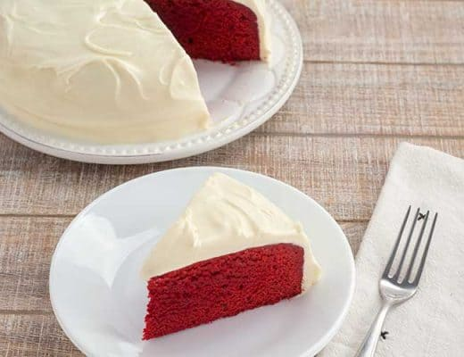 Slice of Instant Pot red velvet cake on white plate with cake in background.