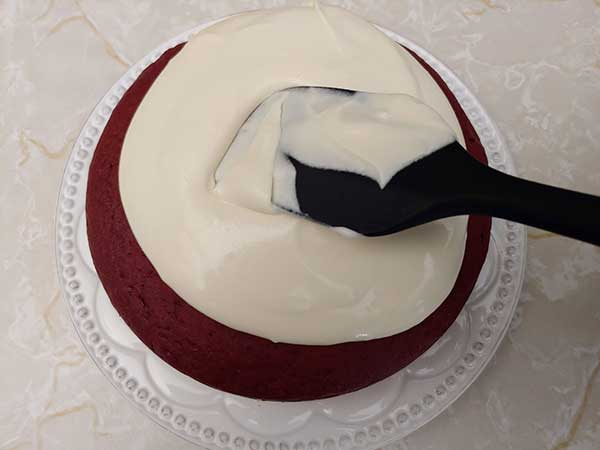 Icing cake on white plate with rubber spatula.