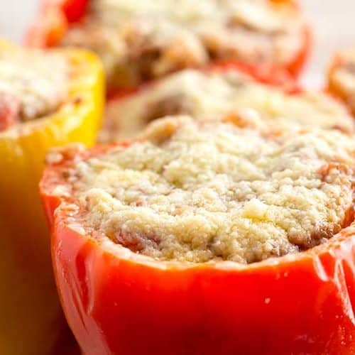 Five pressure cooker stuffed peppers topped with parmesan on white plate.