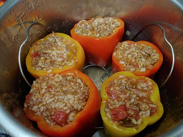 Uncooked bell peppers filled with sauce mixture in Instant Pot.