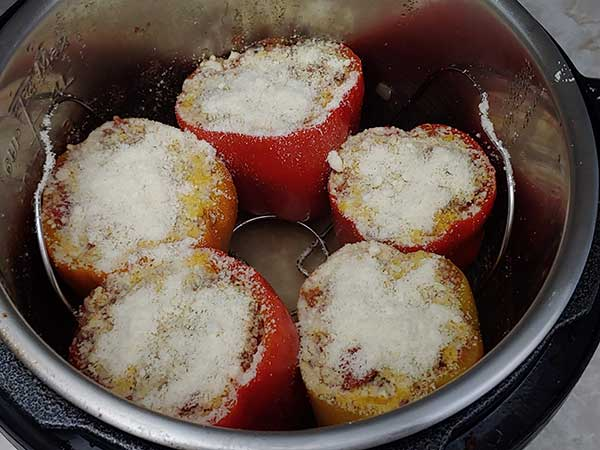 Bell peppers filled with sauce mixture and topped with parmesan.