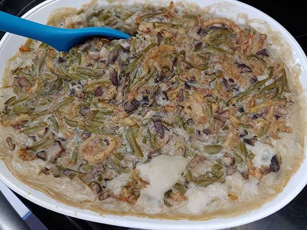 Mixing vegan green bean casserole in dish.