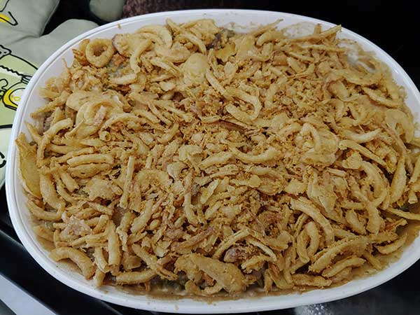 Vegan green bean casserole in dish topped with fried onions.