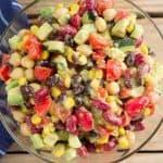 Fiesta bean salad in glass bowl next to blue linen.