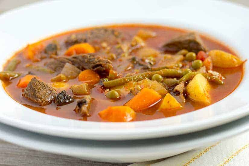 Instant Pot Vegetable Beef Soup in stack of white bowls