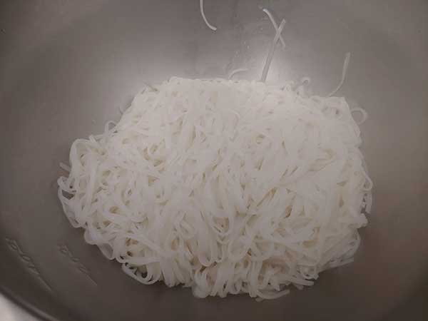 Cooked rice noodles in large mixing bowl.