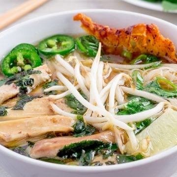 Instant Pot chicken pho in white bowl with garnishes in background.