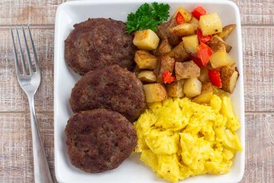 Homemade Italian Sausage patties on plate with eggs and potatoes.
