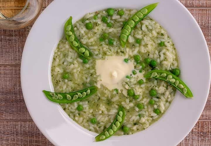 Instant Pot Pea and Mint Risotto in white bowl with glass of wine.
