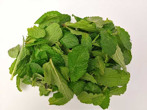 Mint leaves on white cutting board.