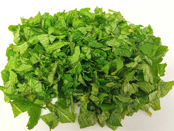 Chopped mint leaves in white cutting board.