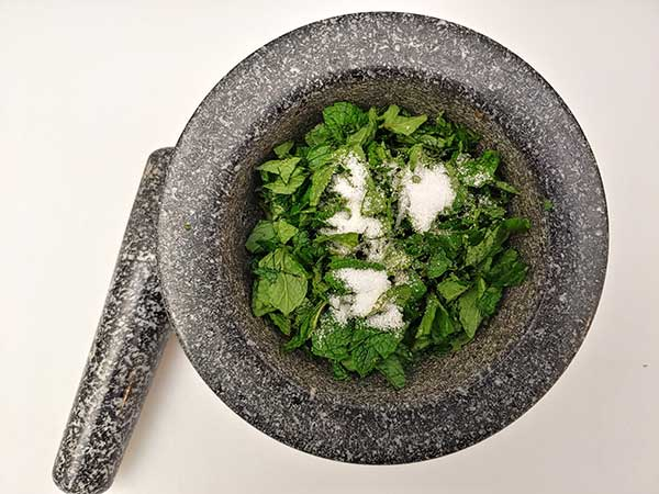 Mint leaves in mortar and pestle topped with salt.