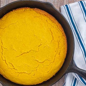 Cornbread in cast iron skillet with linen in background.
