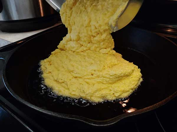 Pouring cornbread batter into hot cast iron skillet.