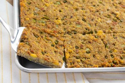 Southern Cornbread Dressing in sheet pan with spatula.