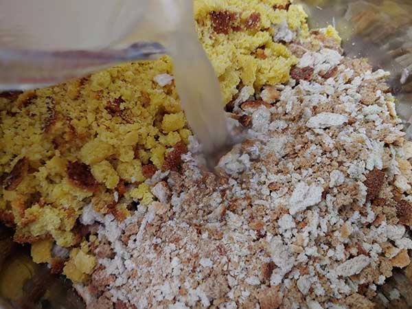 Pouring stock into bowl with cornbread and stuffing mix.